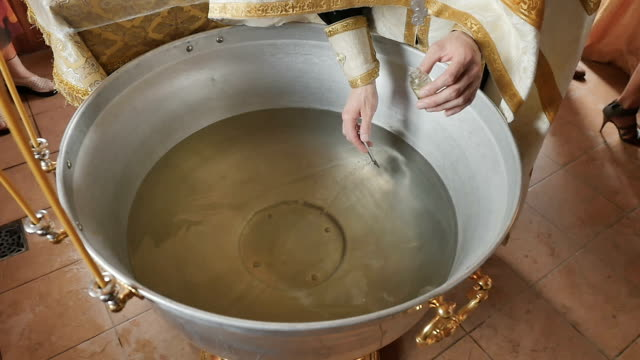 The priest crosses the water in font with brush before the ceremony of baptism video