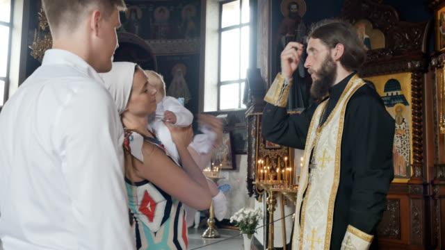 El sacerdote da a un niño a una madre y personas están cruzando en iglesia - vídeo