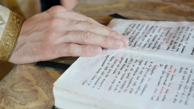 The priest is reding the prayer from bible in church video