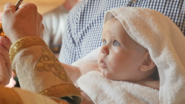 The priest makes a ritual of anointing with oil during the infant baptism video