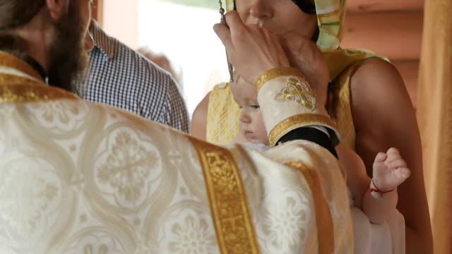 성직자의 유아 세례는 동안 기름으로 기름 부 음 의식 하 게 - 성찬 미사 스톡 비디오 및 b-롤 화면