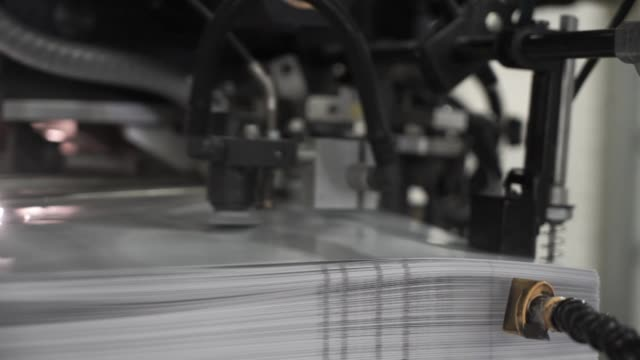 the printing press is loaded with work in the printing house. from the printing press leaves sheets - мембрана клетки стоковые видео и кадры b-roll