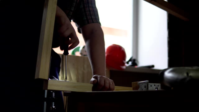 the process of building a wooden table, the carpenter collects the base. - затягивание стоковые видео и кадры b-roll