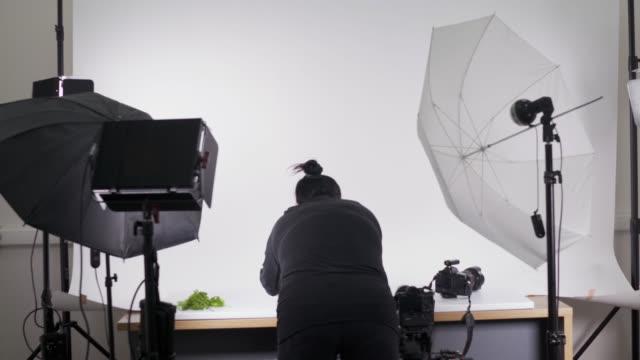 vídeos de stock, filmes e b-roll de o processo da fotografia de comida no fotógrafo de mulher foto studio organiza alimentos - temas fotográficos