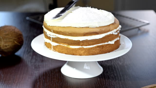 The process of making a cake.Confectioners equates biscuit cream using pastry spatula. video