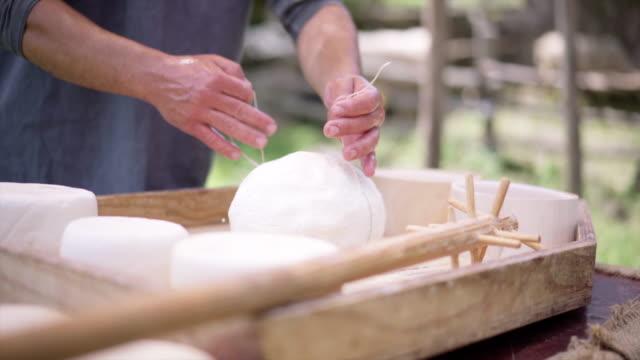 der prozess der herstellung von käse. hausgemachte käse-produzenten in den alpen kombiniert milch, formen und schneidet käse in zwei teilen in holzformen ziehen - brie stock-videos und b-roll-filmmaterial