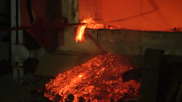 the process of melting metal at the plant in the furnace. workers remove the slag, to obtain a pure alloy - metallurgia video stock e b–roll