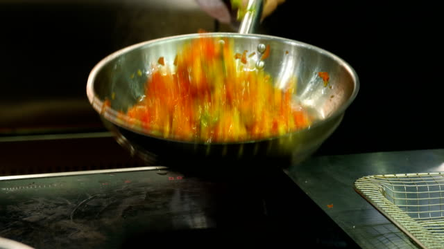 The professional chef fry the vegetables in a frying pan. video