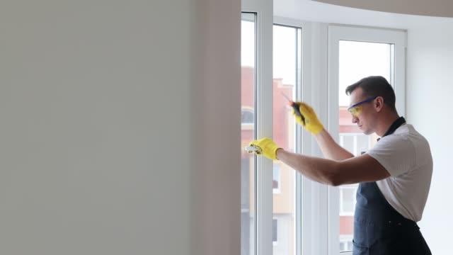 il master professionale cambia la configurazione dalla modalità estiva alla modalità invernale sulla finestra in pvc. prepararsi per l'inverno, riscaldare la casa. riparazione finestre in plastica metallica. sigillatura delle finestre - artigiano video stock e b–roll