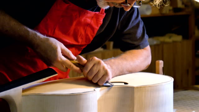 the professional violin master makes a violin with his own hands, uses a clean tree spruce, pine, glasses, planes, tunes strings. - lombardia video stock e b–roll