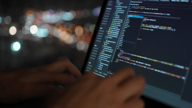 The programmer writes the code for the development of the website, against the background of a beautiful night window in which the city lights are visible in defocus.