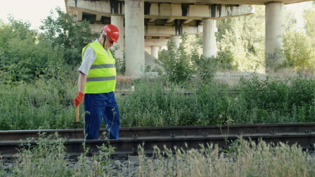 The railroader in uniform checks rails serviceability with hammer in summer day video