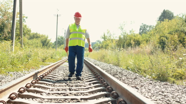 The railroader in uniform walking on railway with hammer and coming at camera video