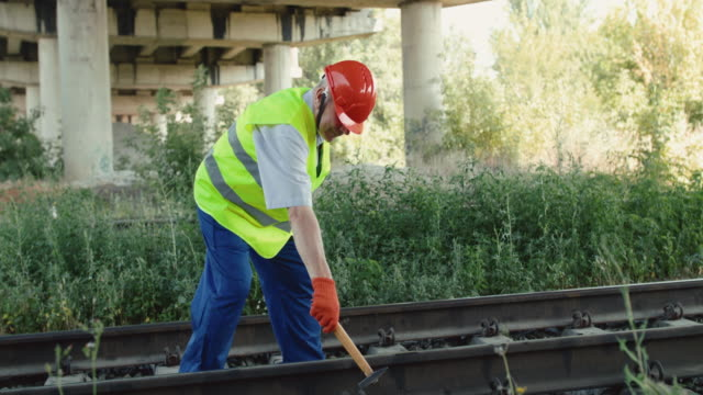 The railroader in uniform walks on track and checks rails with hammer in summer video