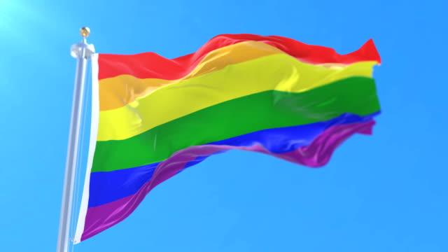 The rainbow flag, LGBT pride flag or gay pride flag waving at wind, loop video