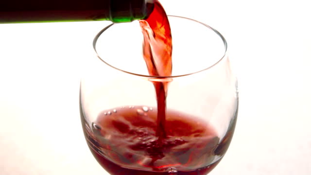The red dry wine is being poured to the cristal clean glass in the restaurant video