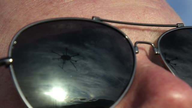 The Reflection of a Hexacopter Drone Flying in a Close-Up Shot of a Caucasian Man's Dark Sunglasses The Reflection of a Hexacopter Drone Flying in a Close-Up Shot of a Caucasian Man's Dark Sunglasses propeller stock videos & royalty-free footage