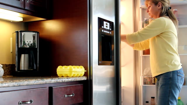 The refrigerator Beautiful mature woman taking an apples from the refrigerator. freezer stock videos & royalty-free footage