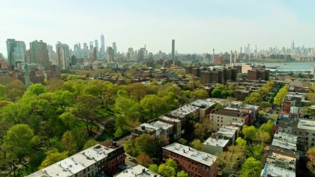vídeos de stock e filmes b-roll de the remote aerial view toward the manhattan downtown financial district from brooklyn, over the residential district and the fort green park - green city