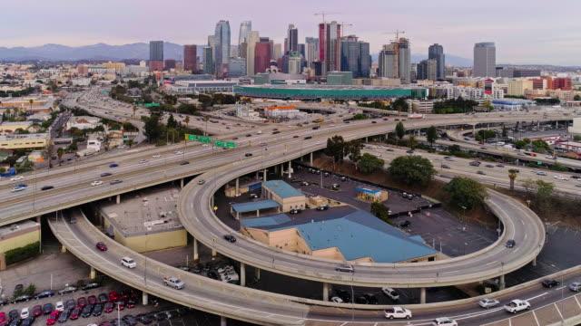 サンタモニカ高速道路とハーバーフリーウェイとトランジットウェイの間の巨大な高架橋を越えて、ウェストワシントン大通りからロサンゼルスのダウンタウンの遠隔風光明媚な空中ビュー - 州間高速道路点の映像素材/bロール