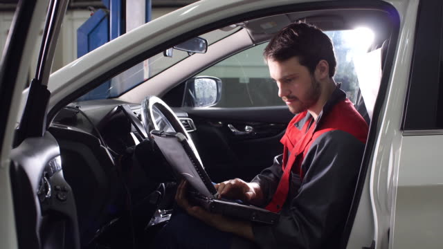 The Repairman, Who Is Dressed in a Working Uniform, Is in the Vehicle and Checks the Gearbox video