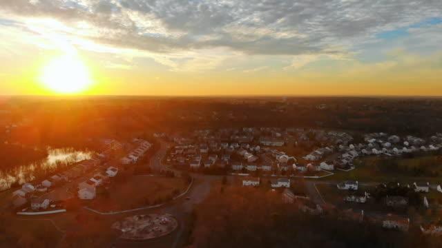 vídeos de stock, filmes e b-roll de os quartos residenciais do alvorecer do por do sol sobre a vila perto da floresta - sol nascente horizonte drone cidade