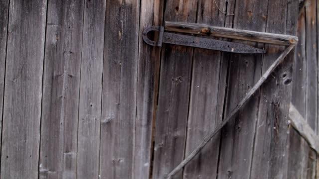 vídeos de stock e filmes b-roll de the rickety door in the old wooden building. snowing - celeiro