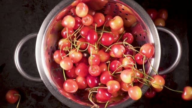 The ripe cherry falls down into a colander slow motion video