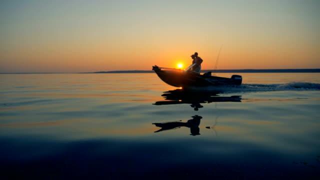 stockvideo's en b-roll-footage met de rijzende zon en twee mannen varen op een vissersboot - boat