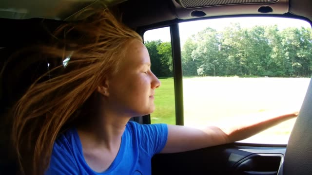 The roadtrip. Long-haired Caucasian teenage girl riding on the backseat of the car, looking through a window and have fun.