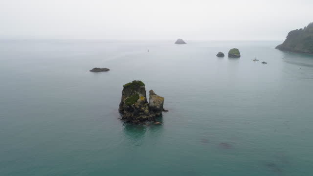 The rocks in the bay with yachts on moorage in the backdrop in the foggy calm tranquil day. The Pacific Ocean near Trinidad, West Coast, California. Aerial video with cinematic orbit camera motion.