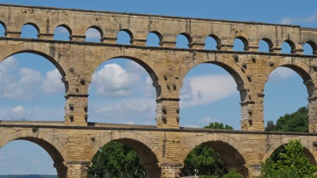 stockvideo's en b-roll-footage met de romeinse brug pont du gard en de gardon rivier, resmoulin, gard, occitanie, frankrijk - pont du gard