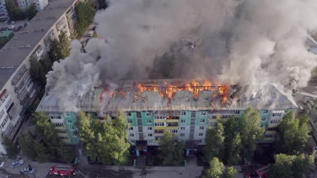 vídeos de stock e filmes b-roll de the roof of a residential house is burning. firefighters extinguish a fire on the roof of a residential high-rise building. - labareda