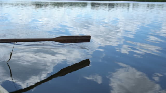 The rowboat floats. Paddle is repelled by water. Paddle close up