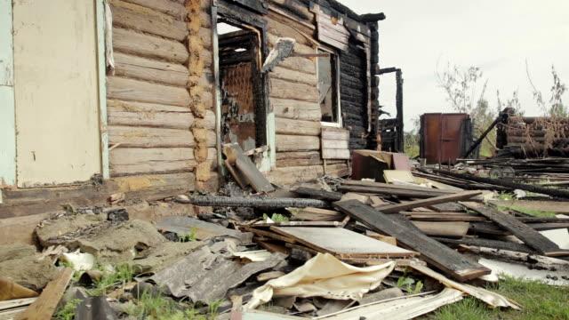 vídeos de stock e filmes b-roll de the ruins of an old wooden house destroyed by fire - cinza