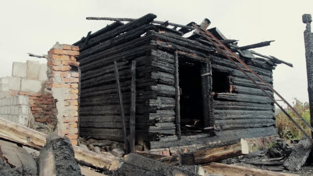 the ruins of an old wooden house destroyed by fire - incendio video stock e b–roll