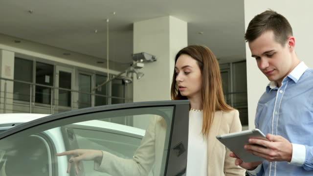 il venditore e la donna parlano di auto in concessionaria - ucraina video stock e b–roll
