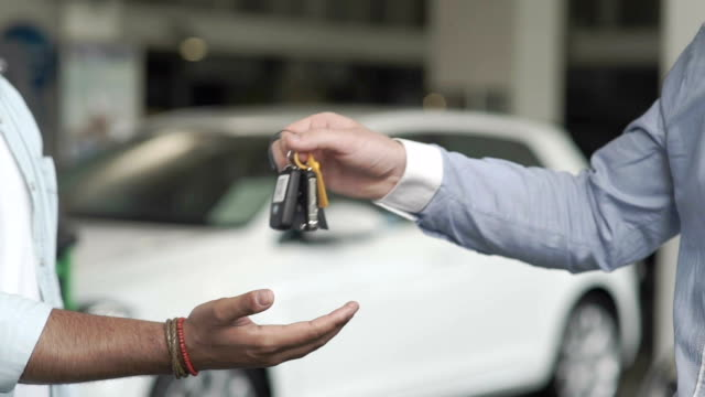 The salesman give the keys to a customer in car dealership Close-up. The seller gives the automobile's keys to the customer. The buyer take a keys in hand. The man just bought a car into car showroom. The man buying the automobile in car dealership and takes a keys. car rental stock videos & royalty-free footage