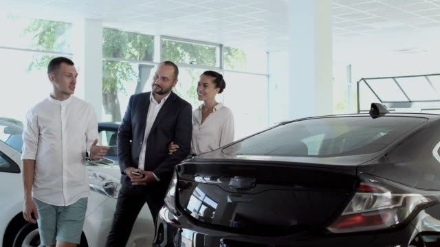 The salesman tells about automobile to a young couple in car dealership video