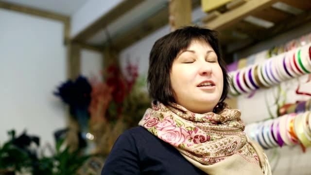 försäljare är i butiken av blommor och dekorationer. - blue yellow band bildbanksvideor och videomaterial från bakom kulisserna