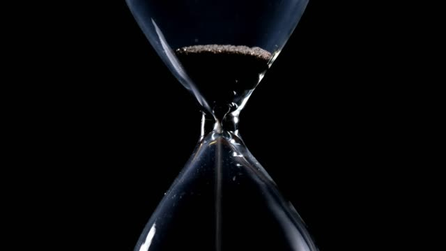 The sand flow in the hourglass until the end of time and sand with black background and lateral light backlight in centered composition The sand flow in the hourglass until the end of time and sand with black background and lateral light backlight in centered composition hourglass stock videos & royalty-free footage