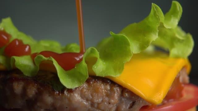 vídeos de stock e filmes b-roll de the sauce pours on a green leaf of lettuce that lies on the burger. - hambúrguer comida