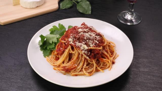 vidéos et rushes de la scène qui saupoudre le fromage en poudre sur les pâtes. - spaghetti bolognaise
