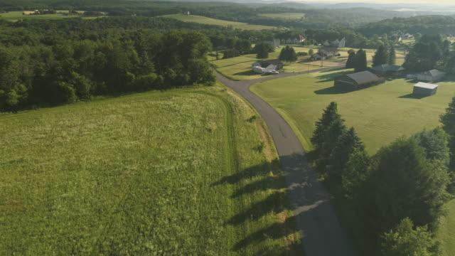 die landschaft luftaufnahme des poconos, monroe county, pennsylvania. die sonnigen sommermorgen. die panorama überblick über das feld und wald auf den kunkletown, dann auf die kleine farm in der nähe von der straße. - pennsylvania stock-videos und b-roll-filmmaterial