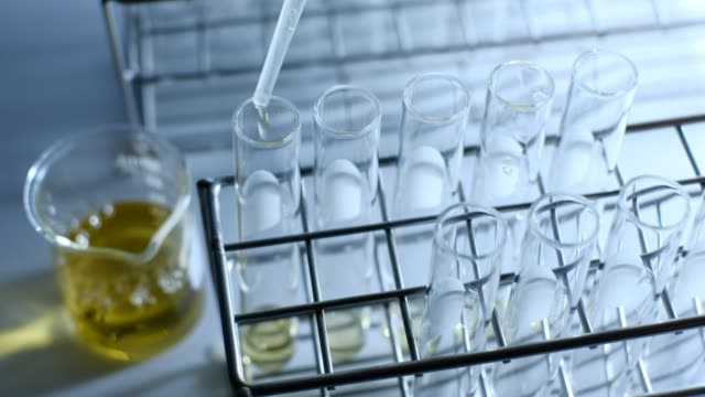 vídeos de stock e filmes b-roll de the scientist dropping the chemical solution in test tube in the laboratory experiment. chemical and oil concept - palm oil bottles