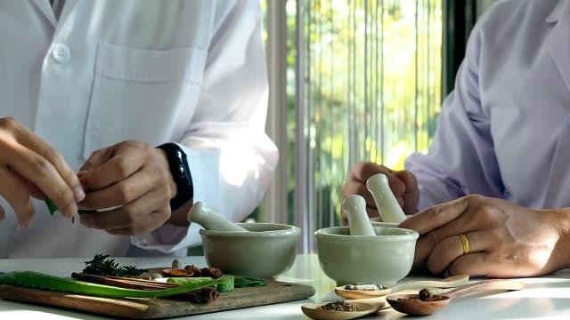 vidéos et rushes de le scientifique ou le médecin fabriquent des plantes médicinales à partir d'herbes en laboratoire sur la table. médecine d'herbes avec la plante le naturel organique dans le laboratoire. - plante aromatique