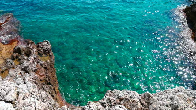 The sea breaks gently on the rocks of the Cap Martin in French Riviera Cote d'Azur French Riviera is situated in the southern eastern part of the mediterranean coast of France and it is famous for its exclusive beaches and its beautiful sea monte carlo stock videos & royalty-free footage