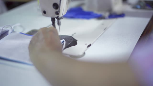the seamstress is sewing the mask - face mask stock videos & royalty-free footage
