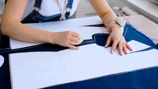 the seamstress working with a cloth and a chalk on the table - cucitura video stock e b–roll
