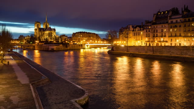The Seine River banks by the Ile Saint Louis and Ile de la Cite with Notre Dame Cathedral at twilight. Paris, France - vídeo